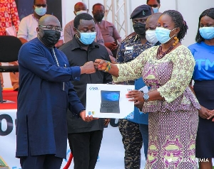 Vice-president Mahamudu Bawumia  handing over one of the laptops to a teacher